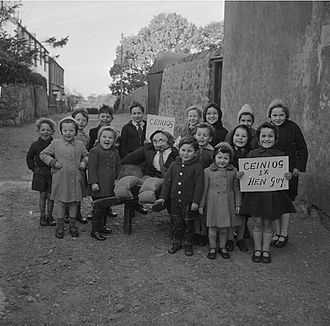 "Guy Fawkes Night - A group of children in Caernarfon, November 1962, stand with their Guy Fawkes effigy. The sign reads ""Penny for the Guy"" in Welsh."