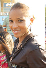 A young black woman in a dark leather jacket, smiling, with large, circular earrings.