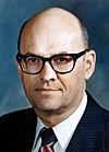 Color photo of a bald man wearing glasses and a suit with a striped tie