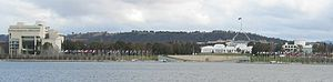 Commonwealth Place, Canberra - Commonwealth Place is located along the south shore of Lake Burley Griffin. The High Court Building is to the left of the image. The White Building is the Old Parliament House, with the new Parliament House behind it. The National Science and Technology Centre commonly called Questacon is the white building with the cylindrical top, located to the right.