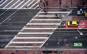 Aerial view of a crosswalk crossing a street at a skewed angle, marked with simple white parallel lines, in San Francisco