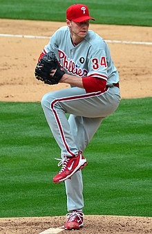A man in a gray baseball uniform with red trim and a red baseball cap holds an unseen baseball with his right hand while wearing a black baseball glove on his left; he has one leg lifted partially in the air