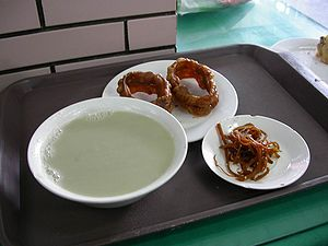 Douzhi - A bowl of douzhi (left) with jiaoquan and preserved vegetable