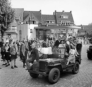Battle of Nijmegen - Nijmegian civilians ride along on a jeep during the advance (20 Sept.).