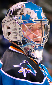 A side shot of an ice hockey player's head and shoulders. He is wearing a blue helmet and a black and blue uniform.