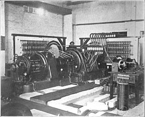 "Goldschmidt alternator - 100 kW Goldschmidt alternator at Eilvese, Germany.  The 250 HP DC electric motor (right), turned the 3 ft. diameter, 5 ton rotor (center), at 4000 RPM. The rotor had 360 poles, and the fundamental frequency of the alternator was 24 kHz.  Complicated ""reflector"" circuits (capacitor banks against walls) forced the machine to produce alternating current at four times this frequency, 96 kHz.  The transmitter was used for transatlantic radiotelegraphy traffic, exchanging Morse code messages with a similar Goldschmidt station at Tuckerton, New Jersey, USA During World War I it was Germany's main communication channel to the outside world, and was used for diplomatic negotiations between Woodrow Wilson and Kaiser Wilhelm II  leading to the Armistice."