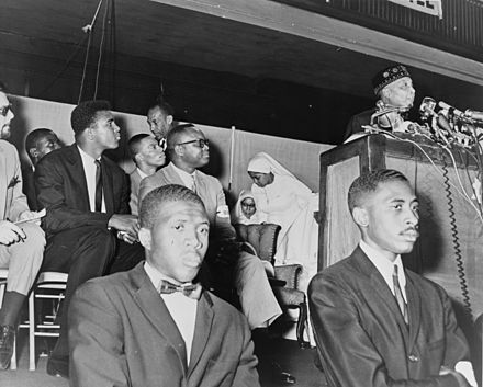 Ali (seen in background) at an address by Elijah Muhammad in 1964 Elijah Muhammad and Cassius Clay NYWTS.jpg