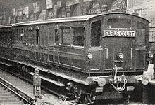 Une photographie trois quarts en noir et blanc d'un train à l'arrêt dans une gare, montrant le wagon d'extrémité avec des fenêtres à l'extrémité.