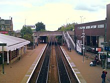 A view from a bridge down onto the railway tracks of Falkirk Grahamston Station. The main building on the left and a waiting room on the right side of the tracks with another road bridge in the distance