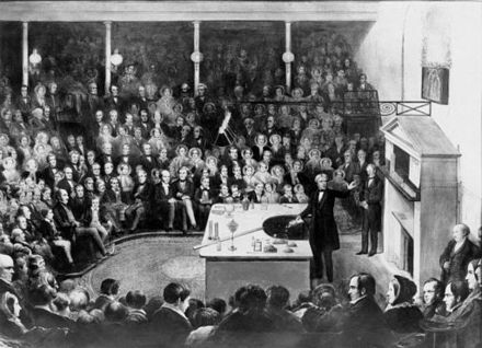 Michael Faraday delivering a Christmas Lecture at the Royal Institution in 1856. Faraday Michael Christmas lecture.jpg