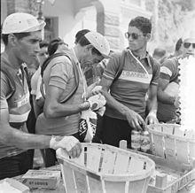Fausto Coppi, entouré de Giovanni Corrieri et Mario Baroni, mange une orange durant le Tour de France 1952
