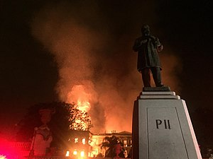 "This photo shows a large, tall building, the National Museum of Brazil, engulfed in flames. To the left of the image, the red glow of fire-truck lights can be seen. In the foreground, to the right, there is a statue of Emperor Pedro II, the name ""Pedro II"" engraved on its base."