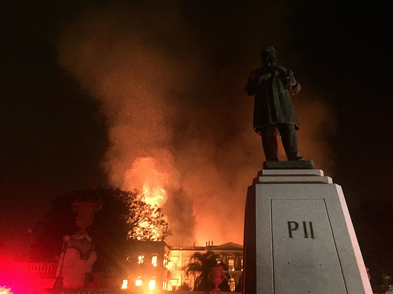 "Photograph of a a large, tall building—the National Museum of Brazil—engulfed in flames; to the left of the image, the red glow of firetruck lights can be seen; and in the foreground, to the right, there is a statue of Emperor Pedro II, the name ""Pedro II"" engraved on its base"