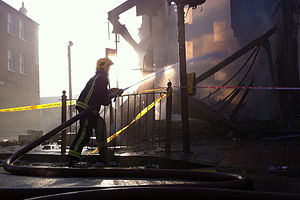 2011 England riots - A firefighter douses a blaze in Tottenham during the aftermath of the initial riot