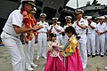 Flickr - Official U.S. Navy Imagery - The CO of USS George Washington presents coins to children dressed in traditional Korean costume at a welcome ceremony.jpg