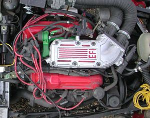 Ford Cologne V6 engine - Above view of a 2.9 litre; front is to the right: Note the pronounced stagger of the cylinder banks. This is a fuel-injected engine. The plenum chamber is silver, and the fuel rail is painted green.