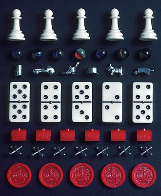 Game - A selection of pieces from different games. From top: Chess pawns, marbles, Monopoly tokens, dominoes, Monopoly hotels, jacks and draughts pieces.