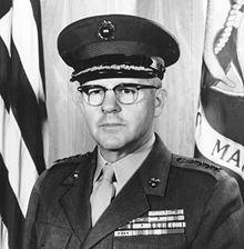A stocky Caucasian man with brown hair and thick glasses in military uniform in front of a flag