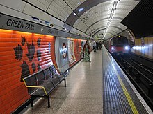 An underground station platform with curving red tiled walls and a white panelled ceiling arching over the track