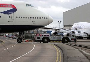 Aircraft ground handling - A ground-handling tug pulls a British Airways Boeing 747-400 at London Heathrow Airport, England