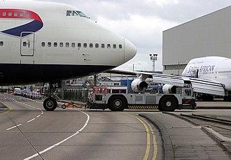 Aircraft ground handling - A ground-handling tug pulls a British Airways Boeing 747-400 at London Heathrow Airport, England