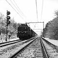 HUA-151002-Afbeelding van een electrische locomotief nr 1213 (serie 1200) met rijtuigen van de N.S. in de (besneeuwde) omgeving van Driebergen. Links een driehoogten-lichtsein.jpg
