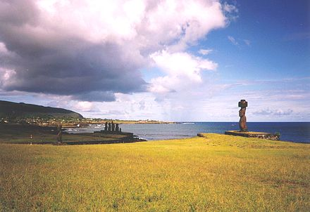 Two ahu at Hanga Roa. In foreground Ahu Ko Te Riku (with a pukao on its head). In the mid-ground is a side view of an ahu with five moai showing retaining wall, platform, ramp and pavement. The Mataveri end of Hanga Roa is visible in the background with Rano Kau rising above it. Hangaroa Moais.jpg