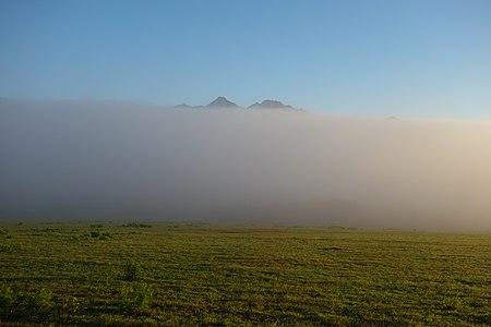 Vrcholky vysokotatranských štítov vyčnievajúce z rannej hmly