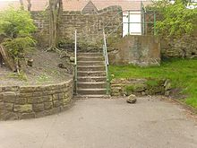 A set of concrete steps leads from an area of concrete path that backs onto a curved sandstone wall surrounding a bank of earth and shrubs on the left and an area of grass and a tree of the right. Behind the steps is another sandstone wall.