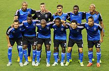 Eleven soccer players wearing blue jerseys and black shorts standing in two lines posing for a pre-match photo.