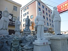 Statues of various kinds (deities, dragons, Confucius, Mao Zedong, and Lei Feng) on display in the front yard of a stoneworking company, one of many dozens of such companies that line the Hui'an Chongwu road.