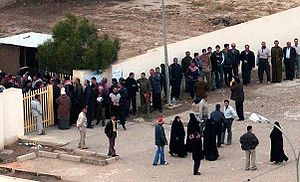 Voter suppression - Voters lining up outside a Baghdad polling station during the 2005 Iraqi election. Voter turnout was considered high despite widespread concerns of violence.