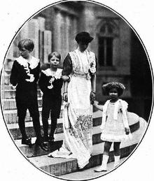 revêtue d'une robe longue de teinte claire, la reine se tient debout aux côtés de ses enfants vêtus en habits d'apparat: Léopold qui regarde vers la droite, Charles qui lui donne le bras et Marie-José qu'elle tient par la main