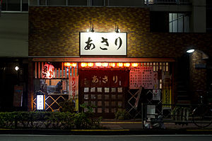 Izakaya - An izakaya in Gotanda, Tokyo. The signboard on the right shows a menu with regular dishes (left) and season's entry – nabe (right).
