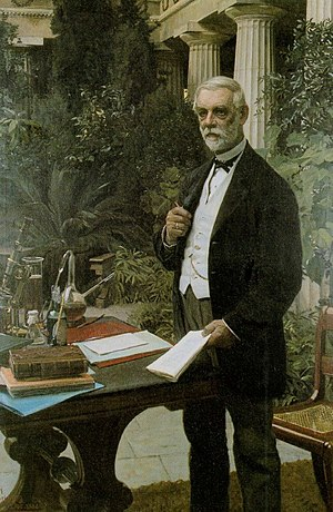 Carlsberg Group - J.C. Jacobsen standing in his winter garden known as Pompeji, next to a table with laboratory equipment, a bottle of lager, a beer glass, and books by Louis Pasteur and Emil Christian Hansen. Painting by August Jerndorff (1886)