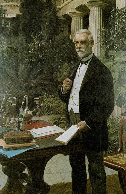 J.C. Jacobsen standing in his winter garden known as Pompeji, next to a table with laboratory equipment, a bottle of lager beer and books by Louis Pasteur and Emil Christian Hansen. Painting by August Jerndorff (1886) - Carlsberg Group