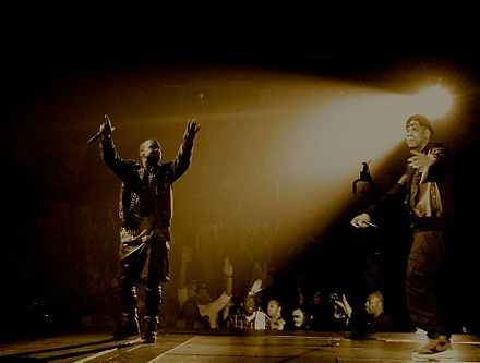 Jay-Z (right) became an internationally renowned hip hop icon in the wake of the deaths of The Notorious B.I.G. and Tupac Shakur in the mid-1990s. Kanye West (left) was mentored by Jay-Z and produced for him, before attaining a similar level of success. Jay-Z Kanye WTT Tour.jpg