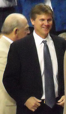 A smiling man in his forties standing and wearing a suit