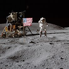Photograph of Young in an Apollo spacesuit on the lunar surface saluting the American flag
