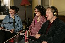 Steven Moffat, Fiona Gillies and Robert Bathurst sitting in a recording studio behind a row of microphones