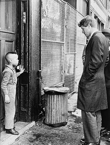 Kennedy speaks with a youth while touring Bedford-Stuyvesant in Brooklyn, N.Y. Kennedy discusses school with young Ricky Taggart.jpg