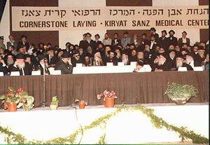 Laniado Hospital - View of the dais at the cornerstone-laying ceremony for Laniado Hospital in 1974. Rabbi Yekusiel Yehudah Halberstam is seen at center left; his son, Rabbi Zvi Elimelech Halberstam (with glasses) is seated to his left.
