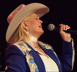 A blonde woman wearing a cowboy hat and a blue jacket with an elaborate floral pattern, singing into a microphone