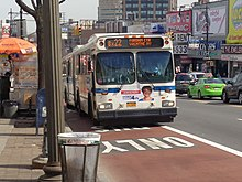 Curbside, red-painted bus lanes on Fordham Road in the Bronx