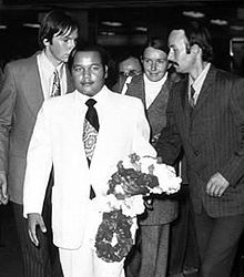 A self-confident young man wearing a white suit, white shirt and dark tie, his left arm holding Indian-style flower garlands; several young Westerners in business suits are standing behind him.