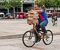 Man carrying boxes on a bicycle.jpg