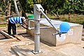 Man pumps water at station provided by USAID (7250565410).jpg