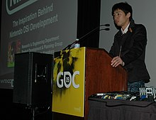 A man stands behind a podium, talking to the audience. Next to him is a projection screen displaying a presentation program slide.