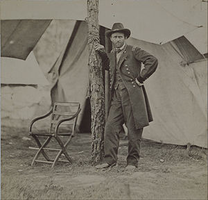 Grant in a standing position is leaning on a tree during the Battle of Cold Harbor.