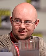 A photograph of a man with a small beard and a bald head, wearing glasses.